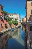 Sikt av byggnader och fartyg framme av en kanal i Venedig Royaltyfria Foton