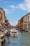Sikt av byggnader som är främst av kanalen, med folk och fartyg i Murano Royaltyfri Fotografi