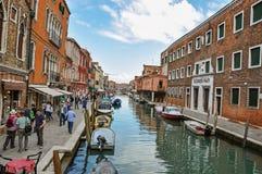 Sikt av byggnader som är främst av kanalen, med folk och fartyg i Murano Arkivbild