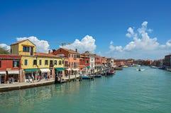 Sikt av byggnader som är främst av kanalen, med folk och fartyg i Murano Royaltyfria Bilder