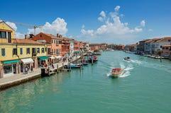 Sikt av byggnader som är främst av kanalen, med folk och fartyg i Murano Royaltyfri Bild