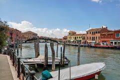 Sikt av byggnader som är främst av kanalen, med folk och fartyg i Murano Arkivbilder