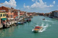 Sikt av byggnader som är främst av kanalen, med folk och fartyg i Murano Royaltyfri Foto