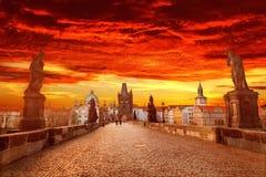 Sikt av Charles Bridge i Prague med dramatiska röda och gul himmel och moln, Tjeckien Prague under solnedgång Arkivfoto