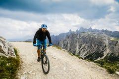 Sikt av cyklistridningmountainbiket på slingan i Dolomites, Tre C Royaltyfri Fotografi