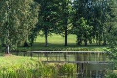 Sikt av dammet i bygd på Sunny Summer Day med metallbron i ram, begrepp av fred och harmoni arkivfoton