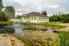 Sikt av dammet och trähusmuseet av det 19th århundradet i Dmitrov Ryssland Arkivbilder