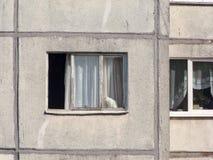 Sikt av de angränsande fönstren av mång--våning en bostads- byggnad från förfallna paneler arkivbilder
