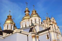 Sikt av de glänsande kupolerna av Stet Michael denkupolformiga domkyrkan i Kiev i strålarna av inställningssolen arkivbild