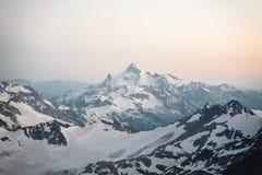 Sikt av de omgeende Elbrus bergen från en höjd av 3800m på solnedgången royaltyfri foto