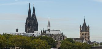 Sikt av de Roman Catholic Gothic Cathedral Kolner Domna och den romanska för Sankt för katolsk kyrka`-brutto `en svala, Arkivbilder