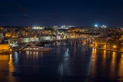 Sikt av de tre städerna vid natt i Malta royaltyfri foto
