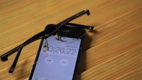 Sikt av den övre klockan och stoppuren för slut på en smartphone mannen startar en stoppur arkivfilmer