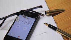 Sikt av den övre klockan och stoppuren för slut på en smartphone mannen startar en stoppur exponeringsglas och reservoarpennalögn lager videofilmer
