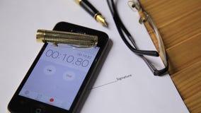 Sikt av den övre klockan och stoppuren för slut på en smartphone mannen startar en stoppur exponeringsglas och reservoarpennalögn stock video