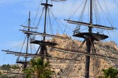 Sikt av den Alicante slotten till och med riggningen av den gamla segelbåten i den Alicante hamnen Arkivbild