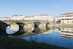 Sikt av den Arno flodbanken med arkitekturbyggnader och broreflecttions Arkivfoto
