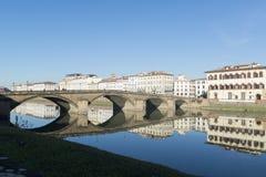 Sikt av den Arno flodbanken med arkitekturbyggnader och broreflecttions Fotografering för Bildbyråer