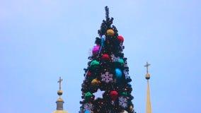 Sikt av den beautifully dekorerade högväxta julgranen mot kyrka, följd stock video