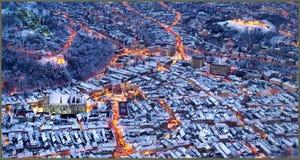 Sikt av den Brasov mitten i en vinternatt, Rumänien Tampa bergöverkant arkivbilder