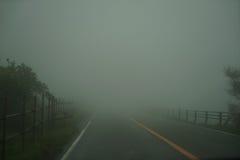Sikt av den dimmiga körbanan och staketet, medan köra till och med den lokala vägen på regnig och dåligt väderdag på Mount Aso om Arkivfoton
