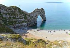 Sikt av den Durdle dörren, en naturlig kalkstenbåge på den Jurassic kusten nära Lulworth i Dorset, England Fotografering för Bildbyråer