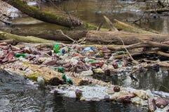 Sikt av den förorenade lilla skogfloden med mycket olik plast- avskräde Miljöföroreningproblem arkivfoto
