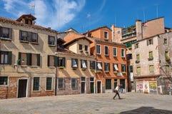 Sikt av den gamla färgrika byggnader och gångaren i en fyrkant, på Venedig Fotografering för Bildbyråer