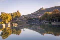 Sikt av den gamla Tbilisien Metekhi och fästningnarkikaen från bron av världen Arkivfoto