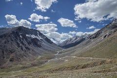 Sikt av den gröna dalen med den slingriga floden och väg och stor snöig bergbakgrund Arkivfoto