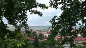 Sikt av den grekiska byn mellan gröna träd arkivfilmer