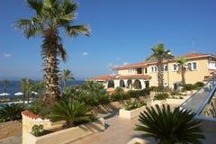 Sikt av den gula byggnaden, det blåa havet och gröna palmträd i hotellet, Grekland arkivbilder