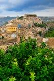 Sikt av den härliga byn Ragusa med grön trädförgrund Royaltyfri Bild
