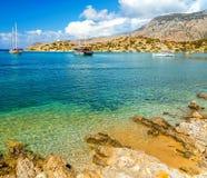 Sikt av den härliga fjärden i den panormitisSymi ön, skepp och fartyg på ankaret, Grekland royaltyfri fotografi