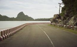 Sikt av den härliga roterande vägen nära havet och berget, abstrakt tappning filtrerad bild Royaltyfri Bild