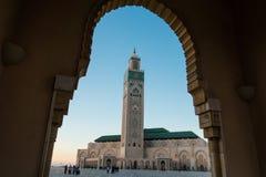 Sikt av den Hassan II moskén som inramas av bågen av en stor port Arkivbilder