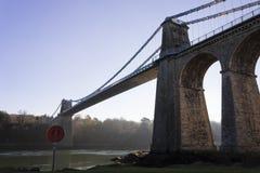 Sikt av den historiska Menai upphängningbron, ö av Anglesey, Wales Royaltyfri Fotografi