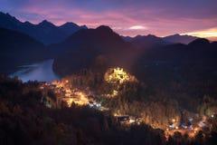 Sikt av den Hohenschwangau slotten och sjön Alpsee Arkivfoto