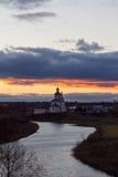Sikt av den Kamenka floden och kyrkan på solnedgången i sen höst Suzdal Ryssland arkivfoto