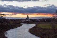 Sikt av den Kamenka floden och kyrkan på solnedgången i sen höst Suzdal Ryssland royaltyfri bild