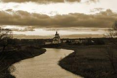 Sikt av den Kamenka floden och kyrkan på solnedgången i sen höst Suzdal Ryssland royaltyfria bilder