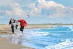 Sikt av den lyckliga unga familjen som har gyckel på stranden Royaltyfri Bild