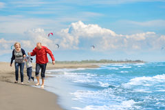Sikt av den lyckliga unga familjen som har gyckel på stranden Royaltyfria Bilder
