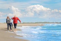 Sikt av den lyckliga unga familjen som har gyckel på stranden Royaltyfri Foto