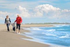 Sikt av den lyckliga unga familjen som har gyckel på stranden Arkivbilder