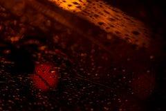 Sikt av den moderna staden till och med fönstret på en mycket mörk stormig natt Begreppsliv av en modern stad, stads- trafik arkivfoton