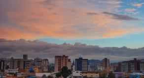 Sikt av den molniga solnedgången i den nordliga delen av staden av Quito Royaltyfri Fotografi