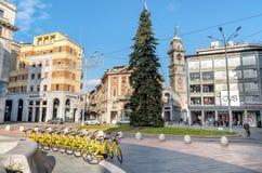 Sikt av den Monte Grappa fyrkanten med högväxt parkering för granträd som och cykellokaliseras i den historiska mitten av Varese Arkivbild
