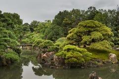 Sikt av den Ninomaru trädgården på den Nijo slotten med bron Royaltyfria Bilder