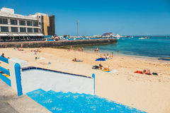 Sikt av den offentliga stranden i Corralejo med porten i bakgrunden Royaltyfri Bild